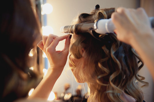 Hairstylist make beautiful curls with curler on light-brown with blonde client's hair. Creating a luxurious evening hairstyle with ringlets of medium length.