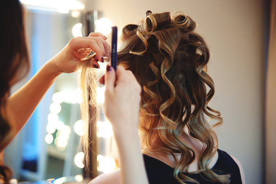 Hairstylist combs client's light-brown with blonde hair. Creating a luxurious evening hairstyle with ringlets of medium length.