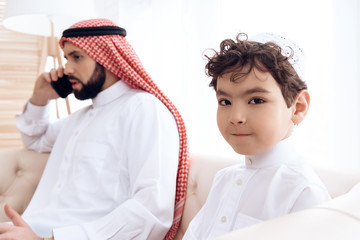 Little boy asks attention of busy Arab father.