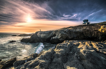 Silhouette of a landscape photographer standing on the rocks along the Malibu beach coastline in California during sunset.  The image depicts an HDR image of the ocean and nature.