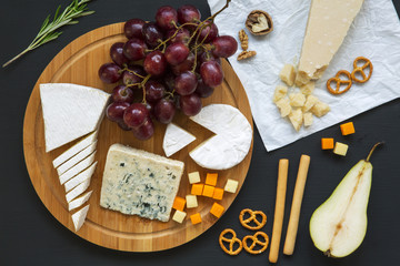 Tasting cheese with fruits, pretzels walnuts and bread sticks on dark background. Food for wine, romantic. Top view. Flat lay.
