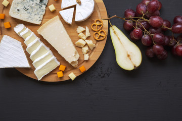 Tasting cheese with fruits, pretzels walnuts and bread sticks on dark background, from above. Food for wine. Top view. Copy space.