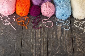 Skeins of yarn assorted colors for needlework on wooden surface