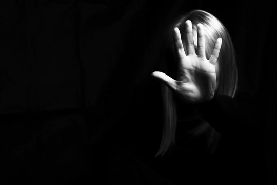 A woman hiding her face and showing gesture stop in a dark. Violence concept. Free space for your text.