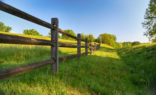 """""""The Fence"""" americana series a rustic wood fence runs along a lush green pasture"""