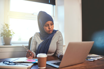 Arabic entrepreneur working on a laptop in her home office