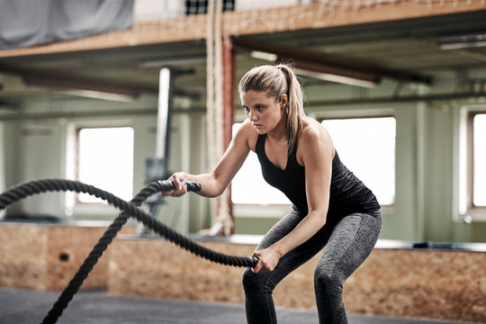 Fit young woman exercising with ropes at the gym
