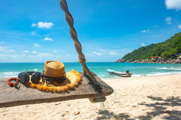 traveling accessory such earphone, music player, hat, sunglass on wooden swing laying under tree on the sea beach, summer time, long weekend, vacation to traveling CONCEPT