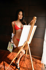 Sexy concept. Sexy painters are drawing in the bedroom. Beautiful girls are thinking of creating art in the home.