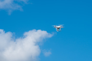 white drone hovering in a bright blue sky, Radio control helicopter with camera