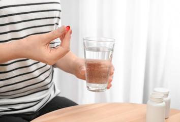 Young woman taking pill, closeup