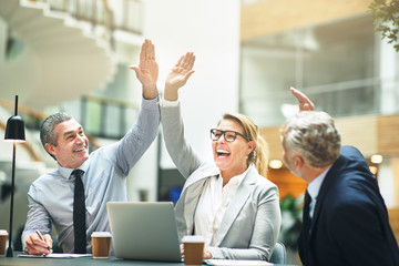 Mature businesspeople cheering and high fiving together in an of