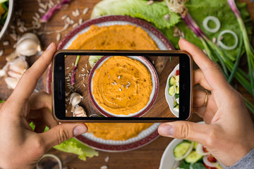 Phone photography of food. Woman hands take photo of lunch with smartphone for social media. Israeli hummus with chickpea, tahini, olive oil. Raw vegan vegetarian healthy dinner