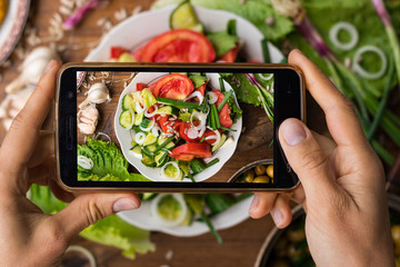 Phone photography of food. Woman hands take photo of lunch with smartphone for social media. Fresh vegetables salad. Raw vegan vegetarian healthy dinner