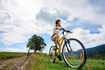 Wide angle view of athlete woman cyclist riding on yellow bicycle on a rural trail, wearing helmet, enjoying valley view. Mountains, big tree and cloudy sky on the background. Copy space