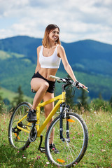 Full length portrait of happy sporty female biker cycling on yellow mountain bike on a grass, enjoying summer day in the mountains. Outdoor sport activity, lifestyle concept