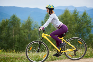 Happy female riding on yellow bicycle on a rural trail in the mountains on summer evening, wearing helmet. Mountains, forests on the blurred background. Outdoor sport activity, lifestyle concept