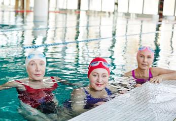 Three healthy mature women in swimwear sitting in water of swimming-pool before training