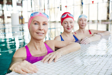 Happy mature swimmer and two more women in swimwear looking at you from swimming-pool