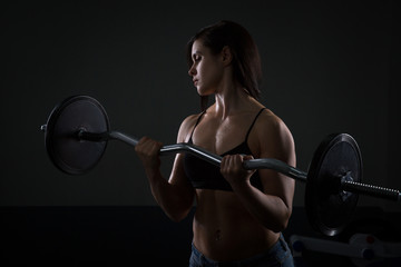 Portrait of athlete girl lifting dumbbells on dark background