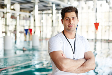 Cross-armed man in activewear looking at camera while having break between trainings by swimming-pool