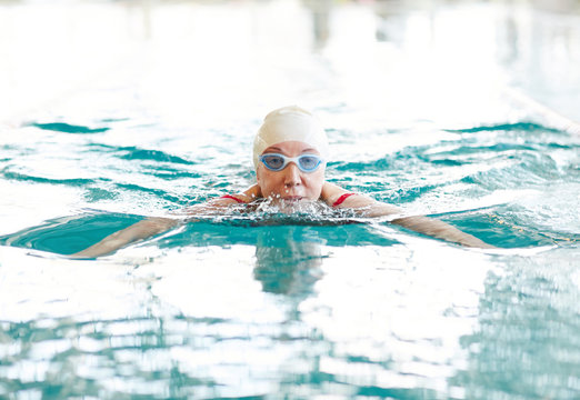 Active woman of senior age spending time by training in swimming-pool
