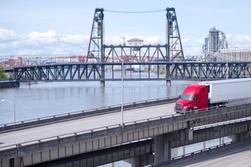 Red big rig semi truck with refrigerator semi trailer transporting cargo on highway overpass intersection along the Willamette River in Portland