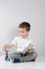 Kind sitzt auf dem Tisch mit dem Buch in der Hand und sucht sich ein Stift aus.