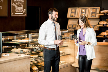 Business couple talking near the counter of the coffee shop