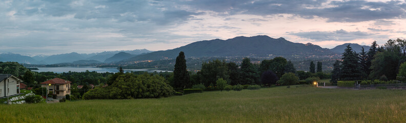 Province of Varese, Italy. Panoramic view at sunrise of the Varese lake, Mount Campo dei Fiori (regional park) and the Sacro Monte (UNESCO site). In the background the snow-covered Alps