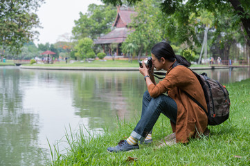 male travelers sitting on green grass near pond in public park, he holding camera on hand and take a photo. concept of travel, trip