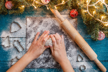 Photo of human hands, rolling pin, dough, spruce branches, garlands