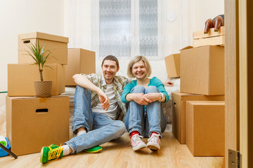 Photo of happy couple sitting on couch among cardboard boxes