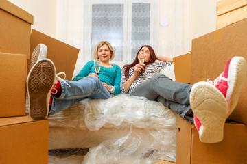 Photo of two girls sitting on sofa among cardboard boxes