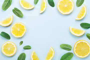 Frame from lemon slices and mint leaves on blue pastel table top view. Ingredients for summer drink and lemonade. Flat lay style. Fototapete