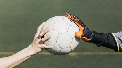 Football player and goalkeeper touching ball
