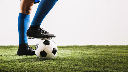 Legs in boots stepping on ball