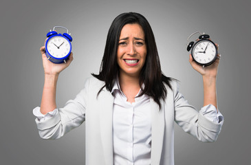Pretty woman holding vintage clock on grey background