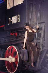 A woman in a vintage black dress with a large suitcase in her hand on an old train. Portrait of a fashionable woman in retro style.