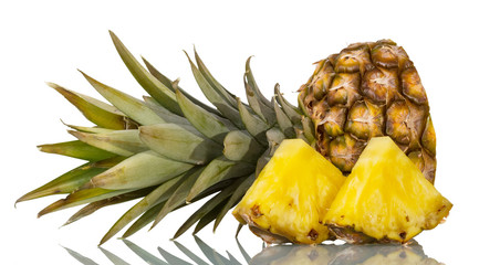 Cut off top of pineapple with leaves, next to slices isolated on white