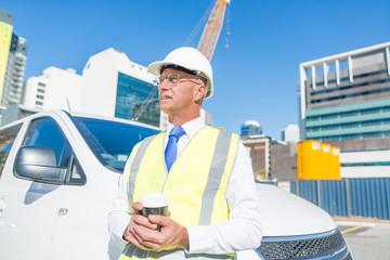 Engineer builder on construction site at sunny day with coffee in hand