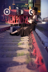 A woman in a vintage black dress sits on the rails near to a large suitcase against the backdrop of an old locomotive. Portrait of a fashionable woman in retro style.