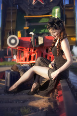 A woman in a vintage black dress refreshed her legs and adjusted her stockings against the backdrop of an old locomotive. Portrait of a fashionable woman in retro style.