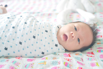 Cute adorable newborn baby boy wrapped or swaddle in a blanket, sleeping and sometime both eyes open in kids bed