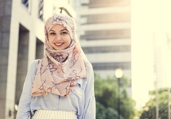 Islamic woman standing and smiling  in the city