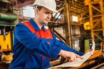 A worker in overalls and a white helmet examines the drawing on the background of an industrial metal plant. The builder is in shape. Male Engineer.