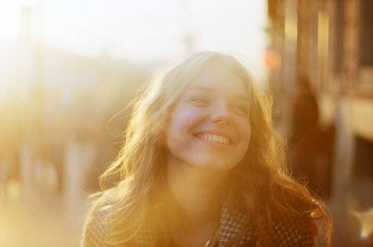 Blonde woman with a beautiful beaming smile backlit by the warm glow of the sun shining down a busy crowdy street, Saint-Petersburg