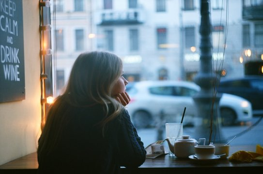 Lonely pensive blonde woman thinking in a coffee shop looking through the window at city street. evening