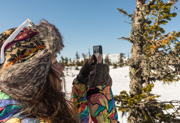 Young woman smiling with smart phone and winter landscape