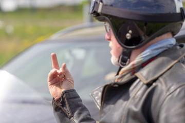 a biker shows his middle finger to a car driver